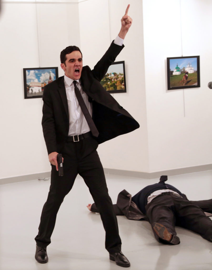 Mevlut Mert Altintas shouts after shooting Andrei Karlov, right, the Russian ambassador to Turkey, at an art gallery in Ankara, Turkey, Monday, Dec. 19, 2016.  (AP Photo/Burhan Ozbilici)